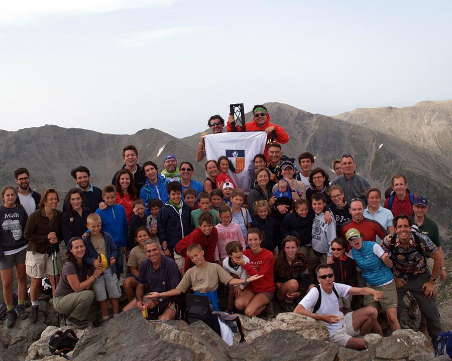 varias personas de distintas edades coronando la cima de una montaña, dos de ellas sujetan una bandera con un escudo